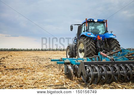 Farmer riding a tractor, a tractor working in a field, agricultural machinery in the work, tractor in the background cloudy sky
