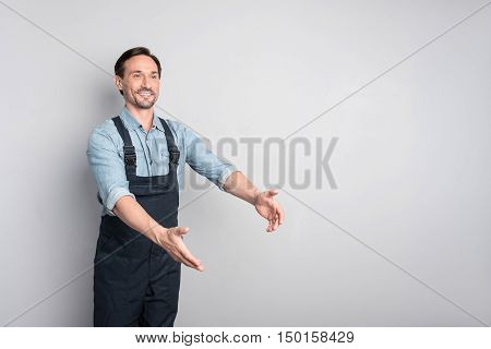 Look here. Handsome cheerful pleasant man moving his hands and smiling while trying to describe something