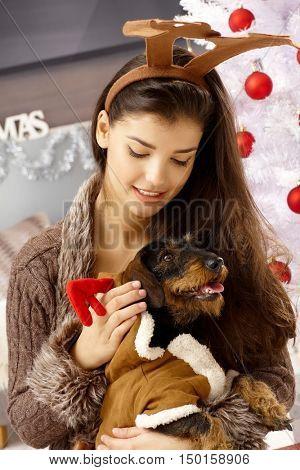 Young woman caressing pet dog at christmas.