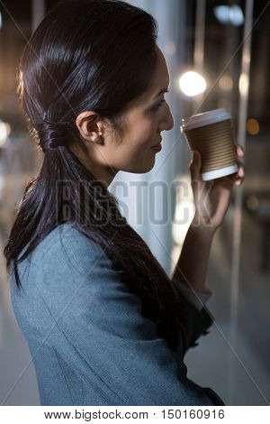 Businesswoman holding disposable coffee cup looking out of window in the office