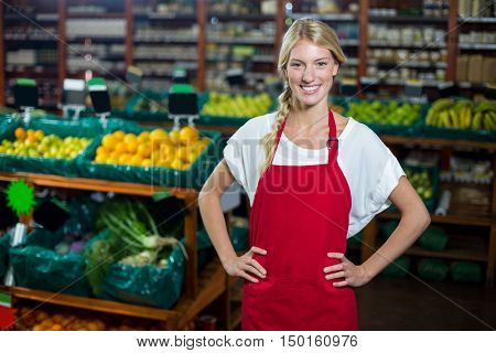 Portrait of smiling staff standing with hand on hip in organic section of supermarket