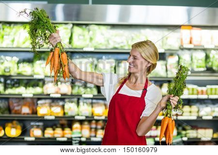 Smiling female staff holding bunch of carrots in organic section of supermarket
