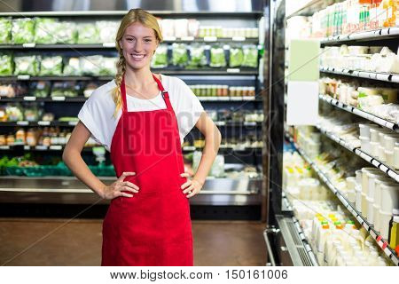 Portrait of smiling female staff standing with hand on hip in grocery section of supermarket