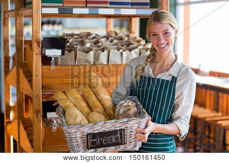Portrait of smiling female staff holding basket of bread at bread counter in supermarket