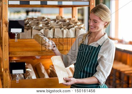 Smiling female staff packing a bread in paper bag at supermarket