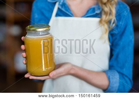 Mid-section of female staff holding jar of honey in supermarket