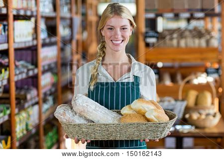 Portrait of happy female staff holding basket of bread at bread counter in supermarket