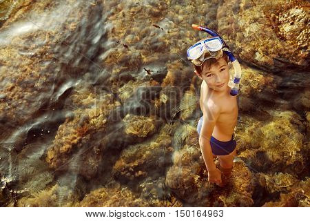 Happy boy enjoys summer holidays at the seaside. A boy swims in the sea snorkelling. Happy childhood.