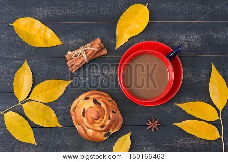 Сup of coffee and a cinnamon bun with amongst autumn leaves on a wooden surface