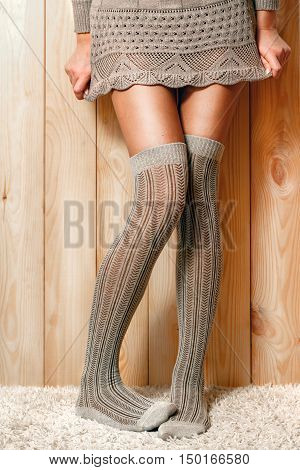 Beautiful, shapely female legs in lace sweater and brown knitted, warm stockings, standing on the carpet