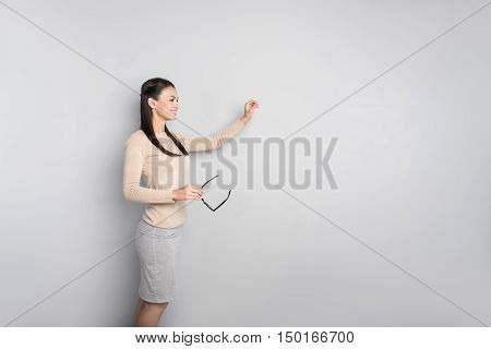 Do it with pleasure. Positive delighted professional female teacher standing near board and conducting a lesson while smiling