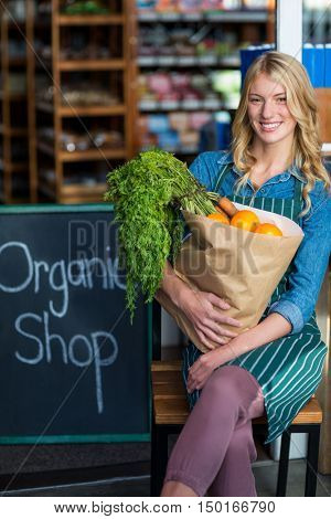 Smiling woman with grocery bag sitting in organic shop