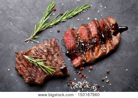 Grilled sliced beef steak with balsamico and rosemary on stone table. Top view