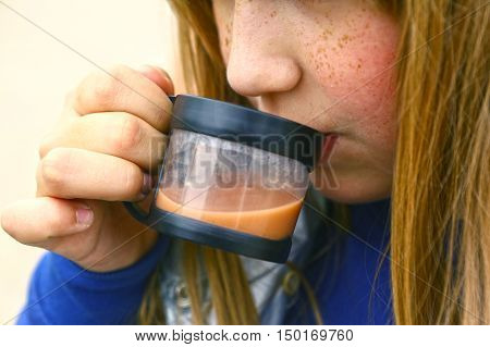 preteen blond girl drink cacao close up photo
