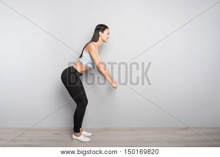 Activate your muscles. Joyful delighted woman smiling and doing sport exercises while standing isolated on grey background