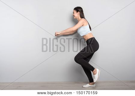 Persistence in mind. Positive confident young woman doing sport exercises and expressing gladness while standing isolated on grey background