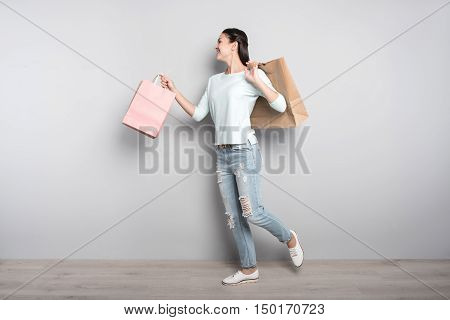Happy after shopping. Positive delighted woman holding packages and going resting after visiting shops while expressing positivity