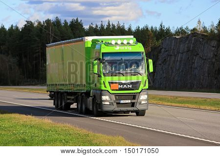 PAIMIO, FINLAND - SEPTEMBER 30, 2016: Lime green MAN TGX 28.520 cargo truck flashes bright high beams briefly when moves along motorway in South of Finland.