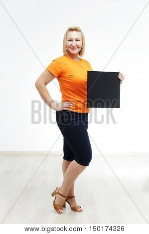 Young overweight woman with sign she is holding against a white background. Plump woman standing and showing empty vertical blank paper in hands, isolated on white background.