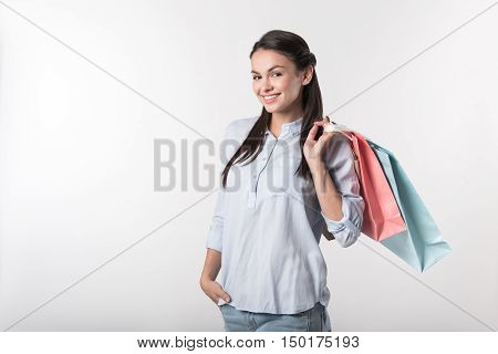 Best way to relieve stress. Cheerful delighted woman holding packages behind her shoulder and smiling while resting after shopping