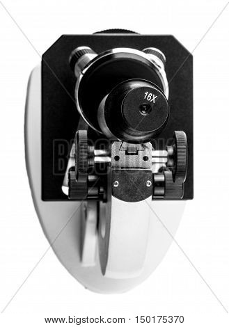 school microscope with lens shot above the cut out on white background