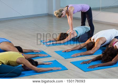 Yoga instructor helping student with a correct pose in fitness studio