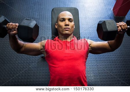 High angle view of male athlete exercising with dumbbells on weight bench