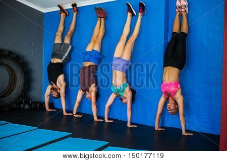 Athletes doing handstand against wall in gym