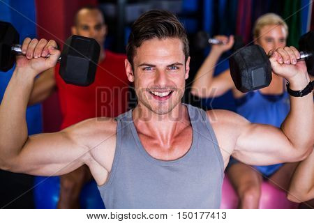 Portrait of smiling man lifting dumbbell while exercising in gym