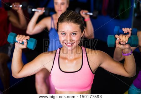 Portrait of smiling woman lifting dumbbell while exercising in gym