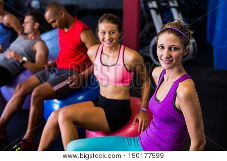 Smiling friends sitting on exercise ball in gym