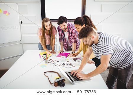 Young male and female editors working in photo editing office