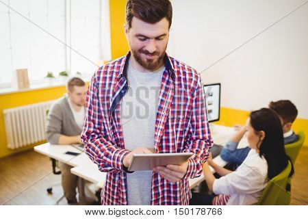 Happy young male executive using tablet computer at creative office