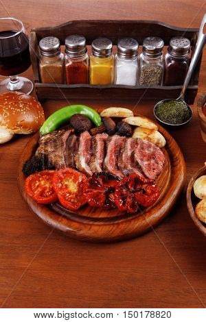 fresh roast bbq beef meat ribeye steak on wooden plate served tomato juice in wooden cup, boiled broccoli, baked tomatoes and potatoes, with white bun, and red wine glass on light walnut wooden table