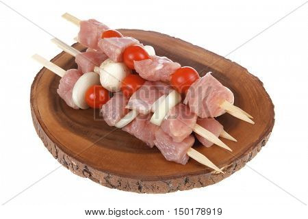 fresh raw meat fillet shish kebab turkey pork pink on skewers tomatoes mushrooms on wooden kitchen plate isolated over white background