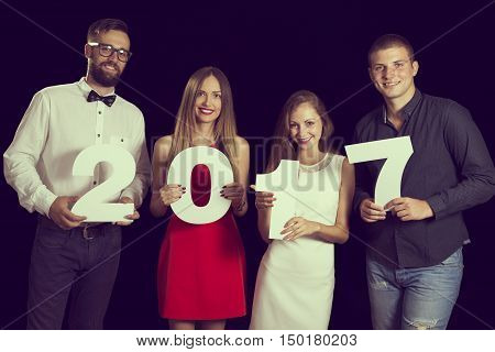 Two beautiful young couples having fun at New Year's Eve Party holding cardboard numbers 2017