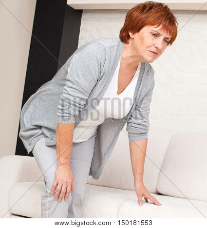 Adult woman has pain in the knee. Mature female at home