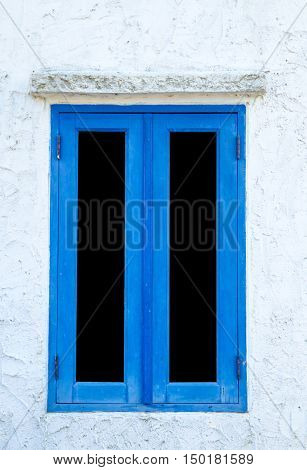 Window with blue shutters on a white wall. Window with closed shutters. Blue window in the wall of the house.