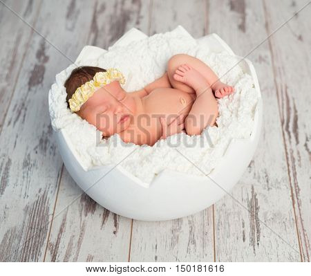 lovely sleeping bare newborn girl with headband with crossed legs in eggshell basket
