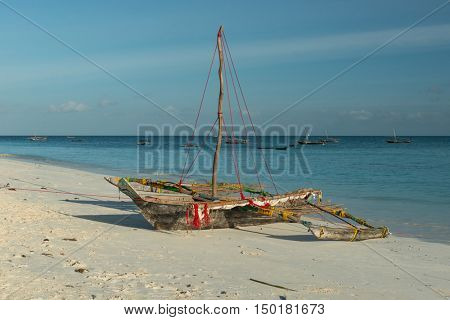 wooden handmade boat with mast and colorful ropes on fishing village shore in Zanzibar