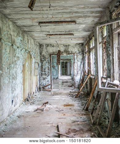 gloomy corridor with broken window frames and debris in Pripyat school