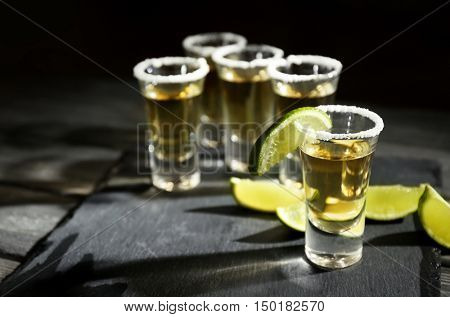 Gold tequila shots with lime and salt on wooden table