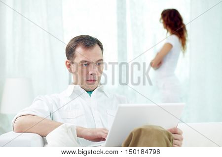 Young man sitting with laptop with woman standing near the window on the background