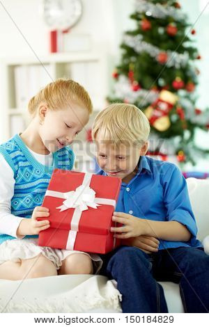 Children opening Christmas gift with curiosity
