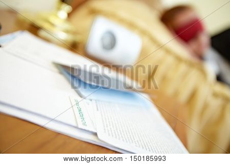 Documents on table with sleeping woman on the background
