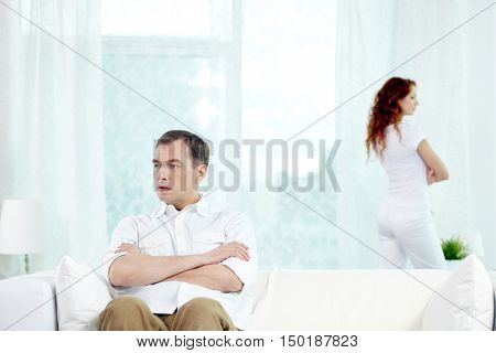 Man sitting on sofa with his wife standing on the background