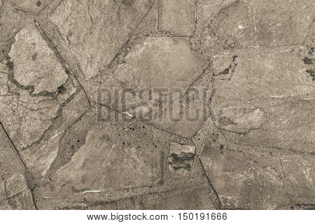 the abstract textured background or wallpaper of beige color from a shapeless stone tile
