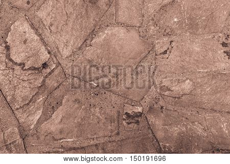 the abstract textured background or wallpaper of brown color from a shapeless stone tile