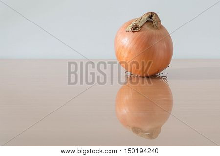 Yellow onion on wooden background and reflection