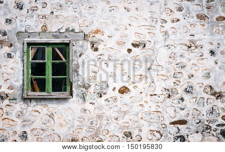 Closed damaged green window on ruined white stoned wall of a deserted house